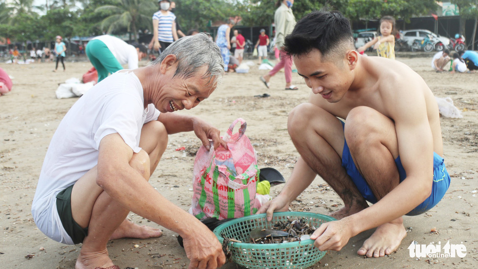 Two men collect shellfish washed ashore after storm at Cua Lo Beach in north-central province of Nghe An, August 30, 2019. Photo: Doan Hoa / Tuoi Tre