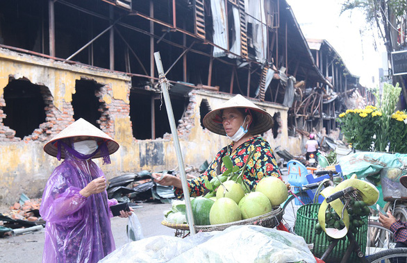 Vendors sell fruits and flowers near the site of an inferno at the Rang Dong Company in Hanoi, Vietnam. Photo: D. Trong / Tuoi Tre