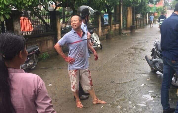 Nguyen Van Dong is seen being held by an officer after killing four members of his brother's family in Hanoi on September 1, 2019. Photo: Tuoi Tre