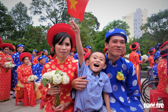 A couple and their son are seen at a mass wedding in Ho Chi Minh City on September 2, 2019. Photo: Vu Thuy / Tuoi Tre