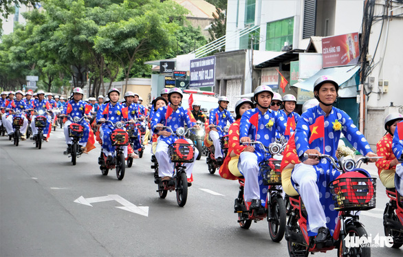 Couples of a mass wedding parade on electric bicycles on a street in Ho Chi Minh City on September 2, 2019. Photo: Vu Thuy / Tuoi Tre