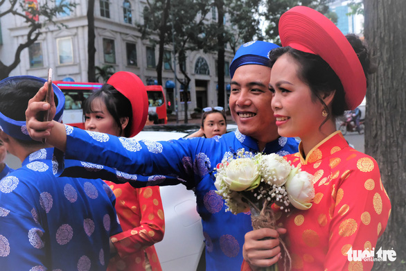 A couple takes a selfie at a mass wedding in Ho Chi Minh City on September 2, 2019. Photo: Vu Thuy / Tuoi Tre