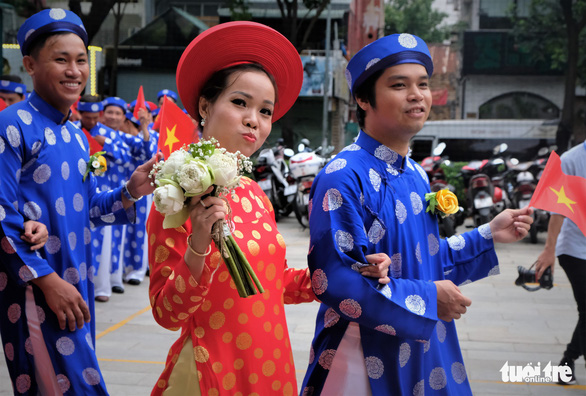 A bride walks beside her groom at a mass wedding in Ho Chi Minh City on September 2, 2019. Photo: Vu Thuy / Tuoi Tre