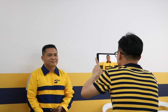 A driver for Vietnamese ride-hailing firm Be has his company ID photo taken at a Be Group office in Ho Chi Minh City on December 12, 2018. Photo: Bui Long / Tuoi Tre