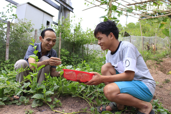 Duc Thien and his oldest adopted soncollect homegrown vegetables in their garden in Quang Tri, central Vietnam. Photo: Cong Trieu / Tuoi Tre