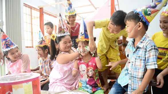 Hieu Thao (middle) and Hoai Thuong (on her left) smile happily in Thao's birthday party. Photo: Tu Trung / Tuoi Tre