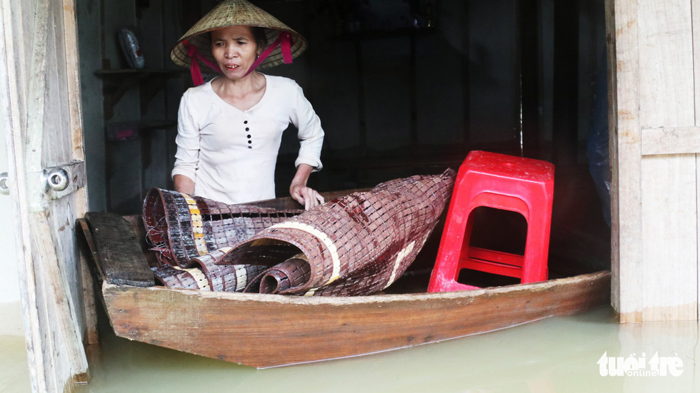 A woman gathers her belongings in her flooded home in north-central Ha Tinh Province. Photo: Doan Hoa / Tuoi Tre