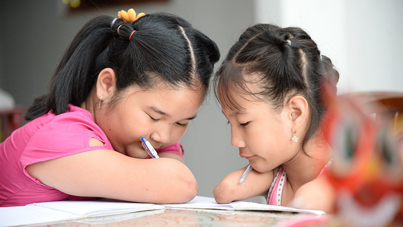 Hoai Thuong (left) teaches Hieu Thao to write by pens in this photo taken in Soc Trang, southern Vietnam. Photo: Tu Trung / Tuoi Tre