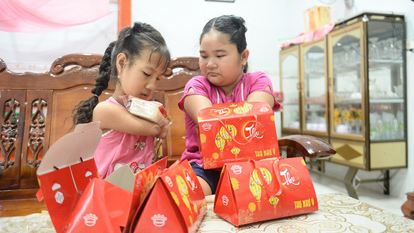 The two girls open Thao's birthday presents in excitement. Photo: Tu Trung / Tuoi Tre