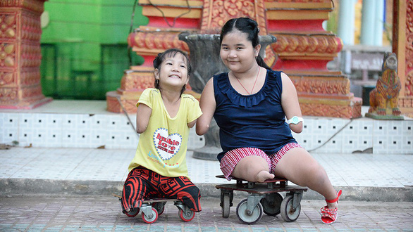 Thuong and Thao smile for a photo on special wheelchairs made by Thuong's father. Photo: Tu Trung / Tuoi Tre