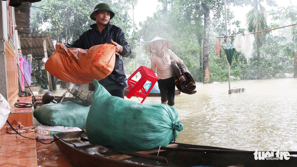 Residents protect their belongings from the water. Photo: Doan Hoa / Tuoi Tre