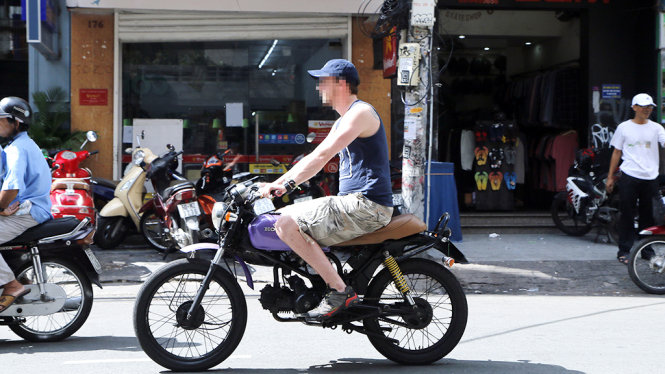 A foreigner rides a motorbike without wearing a crash helmet in Ho Chi Minh City, Vietnam. Photo: Ngoc Duong / Tuoi Tre