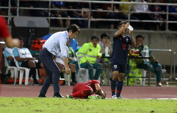 Thai's head coach Akira Nishino tries to call Vietnamese defender Bui Tien Dung to stand up during an injury in their group opener of the Asian second qualifying round for the 2022 FIFA World Cup in Bangkok, September 5, 2019. Photo: N. K. / Tuoi Tre