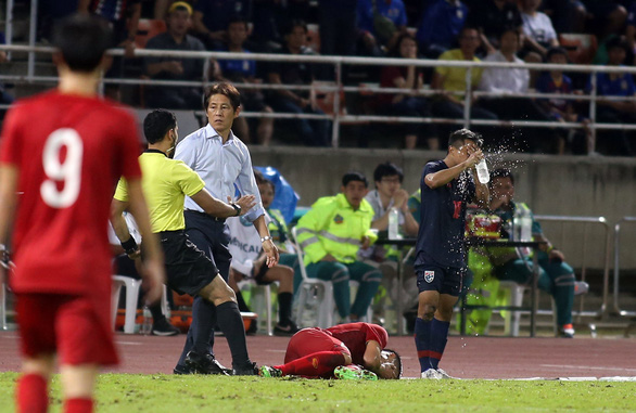 An assistant referee intervenes an intense situation between Thai's head coach Akira Nishino and Vietnamese defender Bui Tien Dung in their group opener of the Asian second qualifying round for the 2022 FIFA World Cup in Bangkok, September 5, 2019. Photo: N. K. / Tuoi Tre