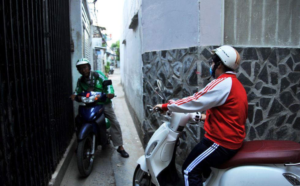 Two motorcyclists take turn to travel on an alley in Binh Thanh District. Photo: Chu Huy / Tuoi Tre