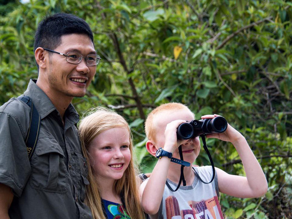 Nguyen Van Luc poses with young foreign tourists in this photo taken from his Facebook account.