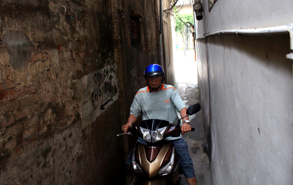 A man rides his motorbike in a small alley in District 1. Photo: Thanh Yen / Tuoi Tre