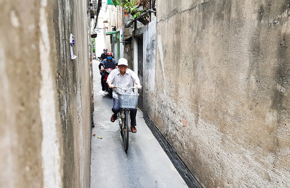 People travel along an alley in Tan Binh District. Photo: Duyen Phan / Tuoi Tre