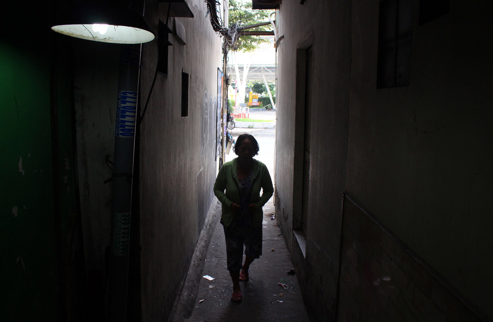 A woman walks along an alley in District 1. Photo: Thanh Yen / Tuoi Tre