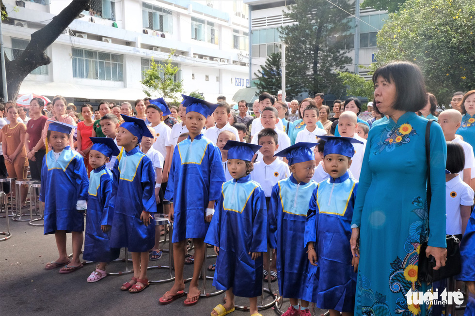 The students and their teacher attend the flag salute. Photo: Canh Toan / Tuoi Tre