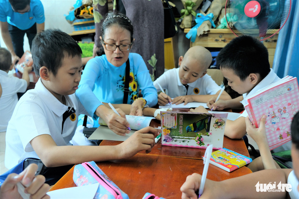 Nguyen Phuong Loan, a teacher in the charity class, teaches the young cancer patients to write. Photo: Canh Toan / Tuoi Tre