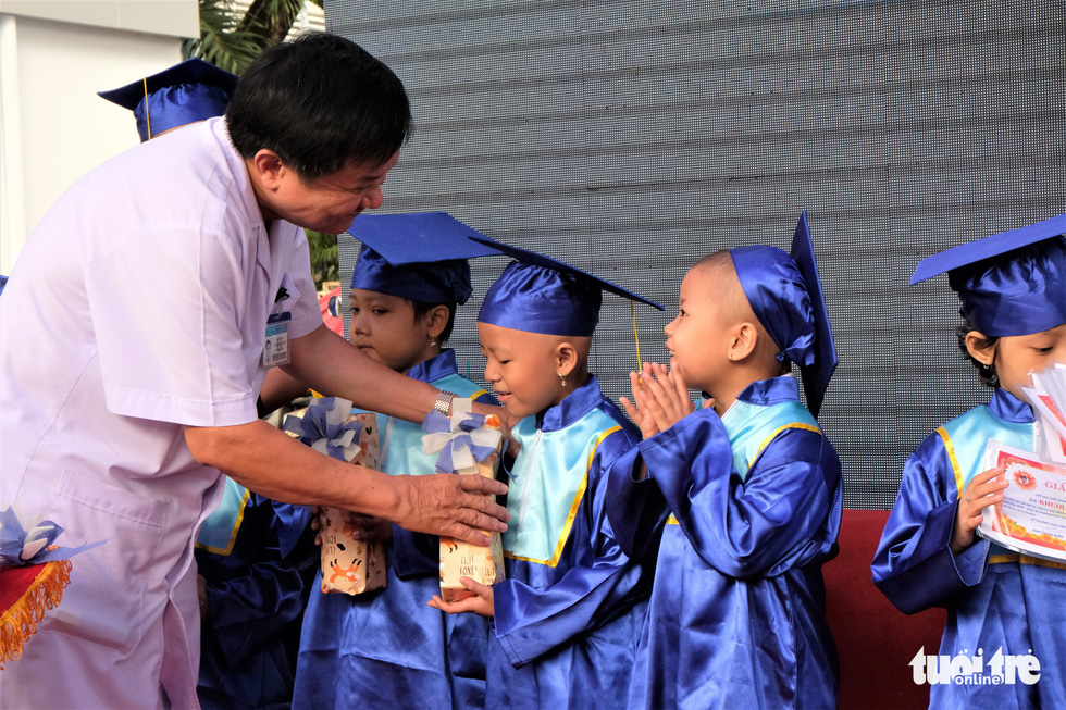 A doctor awards children with prizes for good study results from the previous year. Photo: Canh Toan / Tuoi Tre