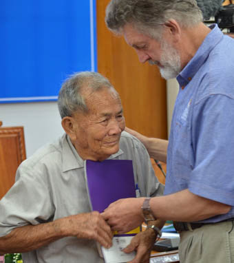 Bob Hall (R) gives a wartime letter to its author, a Vietnamese war veteran, during a visit to Vietnam in 2013. Photo: Truong Dang / Tuoi Tre