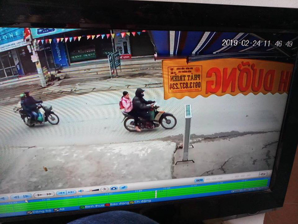 Nguyen Trong Trinh carries the nine-year-old victim on his motorbike in this screenshot taken from security camera footage.