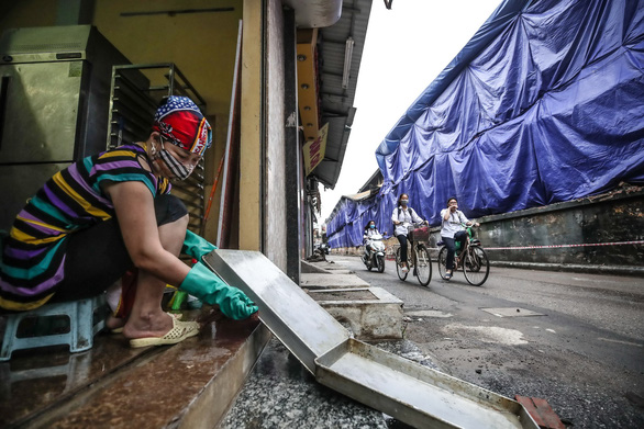A woman living near the Rang Dong Company in Hanoi cleanses her household utensils after a fire on August 28, 2019 that caused up to 27.2 kilograms of mercury from the company's warehouses to be released into the environment. Photo: Nguyen Khanh / Tuoi Tre