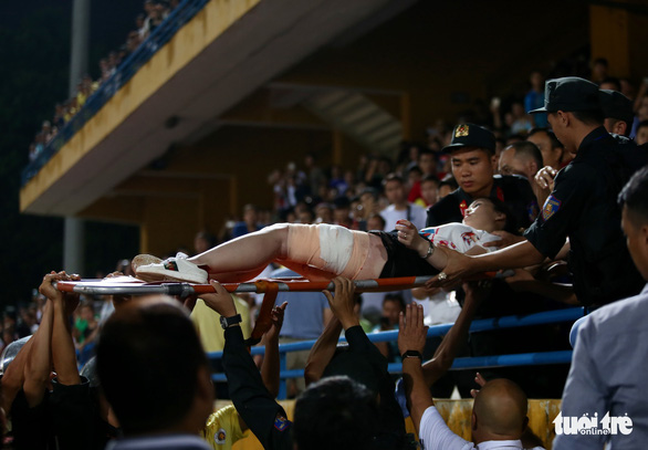 A woman is taken to hospital after being hit by a flare during a V.League 1 game at Hang Day Stadium in Hanoi, September 11, 2019. Photo: Tuoi Tre