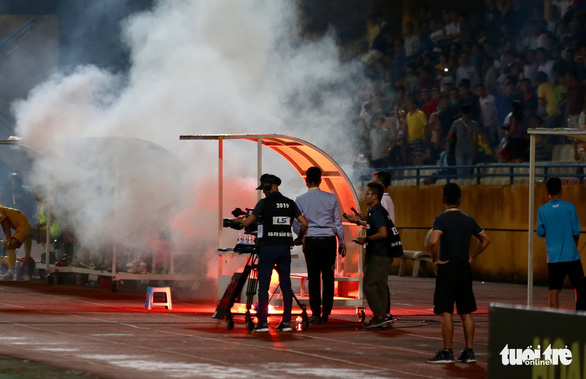 A flare is thrown to the coaching section during a V.League 1 game at Hang Day Stadium in Hanoi, September 11, 2019. Photo: Tuoi Tre