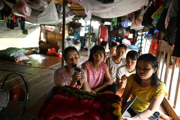 For many Vietnamese migrant workers living on Hanoi's Red River, the camaraderie that comes with selling fruit brings fragments of comfort. Photo: AFP
