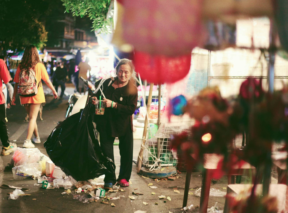 A woman collects waste littered on Hang Ma Street in Hoan Kiem District, Hanoi, September 13, 2019. Photo: Mai Thuong / Tuoi Tre