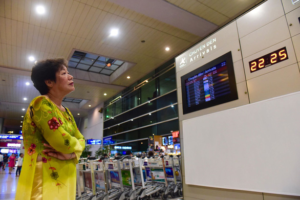 Vu Thi Vinh looks at a flight information display board outside the arrival gate at Tan Son Nhat International Airport in Ho Chi Minh City, September 12, 2019. Photo: Quang Dinh / Tuoi Tre