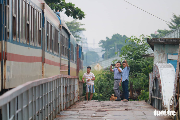 Local people film the last train passing the old Binh Loi Railway Bridge. Photo: Ngoc Phuong / Tuoi Tre