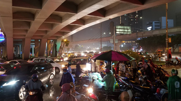 Commuters wait under an overpass for the rain to stop. Photo: Chau Tuan / Tuoi Tre
