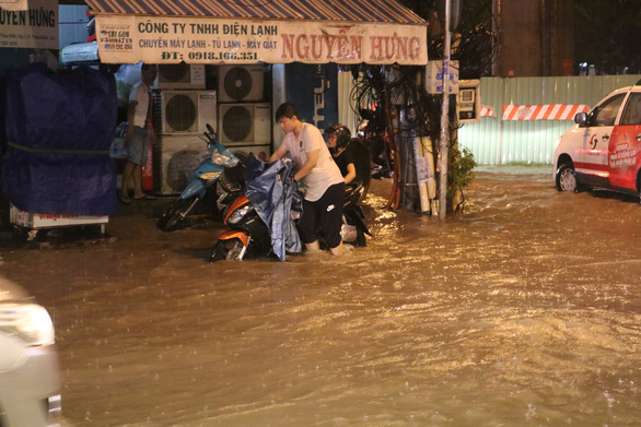 A man pushes his motorbike on Thao Dien Street in District 2. Photo: Thu Hien / Tuoi Tre
