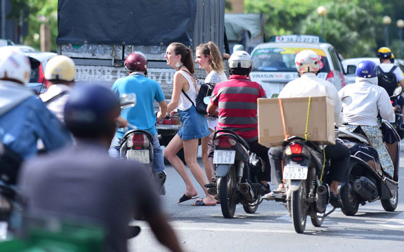 Two foreigners cross road at zebra crossing in ho Chi Minh City. Photo: Quang Dinh / Tuoi Tre