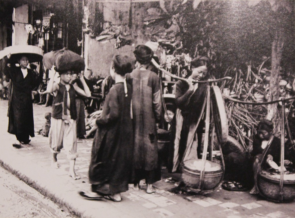 A photo capturing street vendors in Hanoi in 1922 is displayed at an exhibition in Hanoi. Photo: Thien Dieu / Tuoi Tre