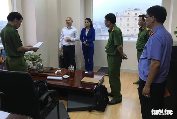 A police officer reads the arrest warrant on Nguyen Thai Luyen (white shirt), chairman of Alibaba Real Estate Corporation, at the firm's headquarters in Ho Chi Minh City, Vietnam, September 18, 2019. Photo: Tuoi Tre Contributor