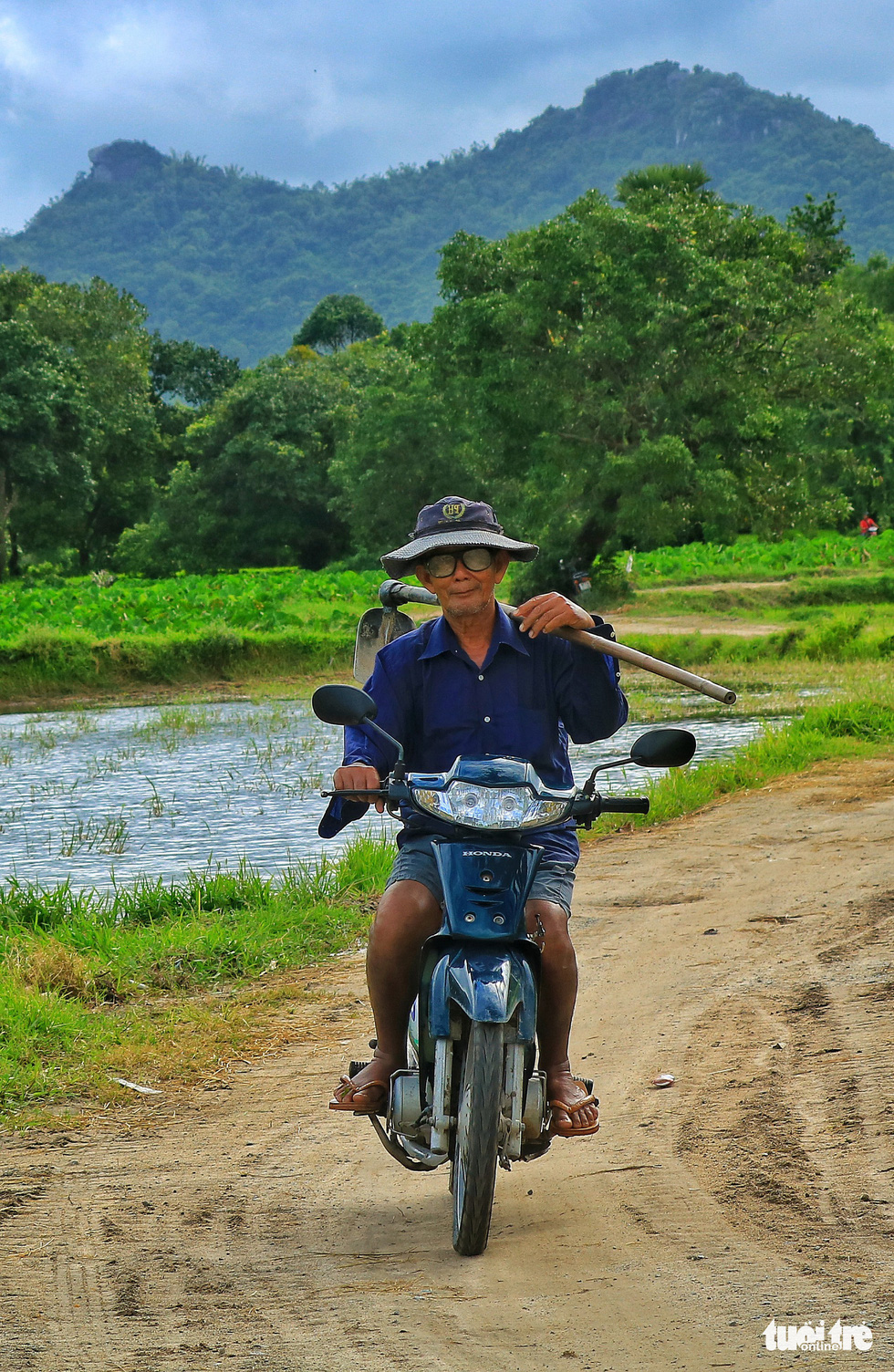 An old man rides a motorbike while shouldering a hoe on a trail amid rice paddies in Tri Ton District, An Giang Province, southern Vietnam. Photo: Nguyet Nhi / Tuoi Tre