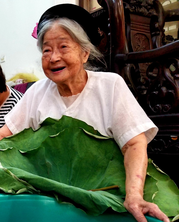 95-year-old Nguyen Thi Dan smiles for a photo while holding a big lotus leaf. Photo: Ha Thanh / Tuoi Tre