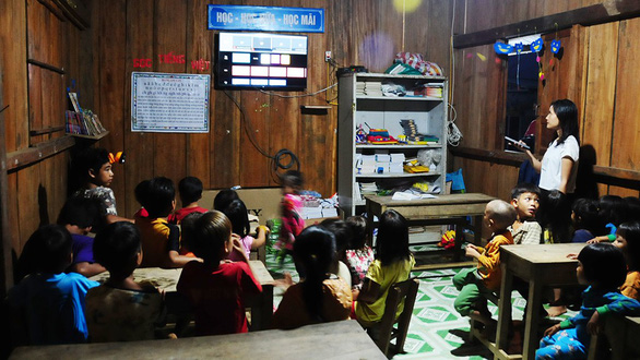 Tra Thi Thu and her students watch TV after dinner. Photo: B.D. / Tuoi Tre