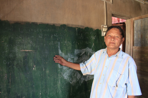 Tran Van Hoa poses in front of the makeshift blackboard in his house in central Vietnam. Photo: Cong Trieu / Tuoi Tre