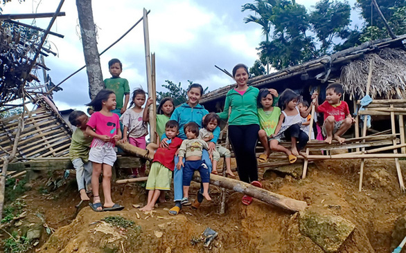 Tra Thi Thu (center) and her colleague Riah Uoi pose with their students in front of their small school in Tak Po Village in this provided photo