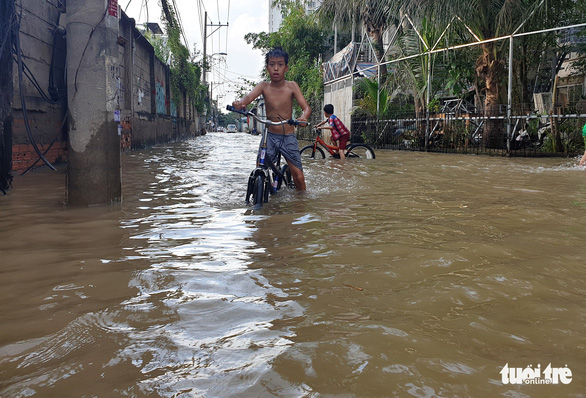 Children cycle on a flooded street in District 2. Photo: Minh Hoa / Tuoi Tre