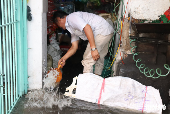 A man scoops water out of his home in District 4. Photo: Xuan Mai / Tuoi Tre