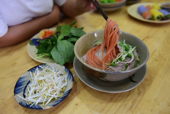 Orange noodles served with beef, vegetables, and mung bean sprouts. Photo: Quang Dinh / Tuoi Tre