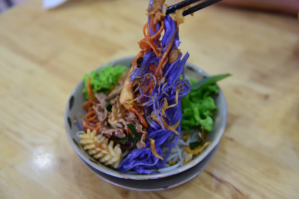 Purple noodles served with seafood in a bowl full of vegetables. Photo: Quang Dinh / Tuoi Tre