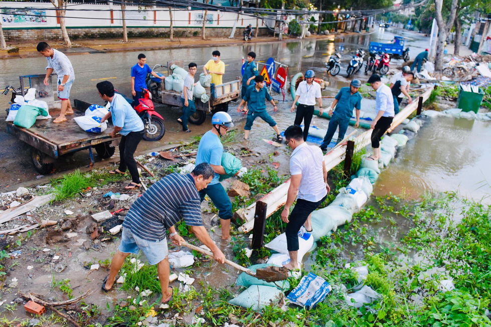 People make an embankment in District 2. Photo: Duyen Phan / Tuoi Tre